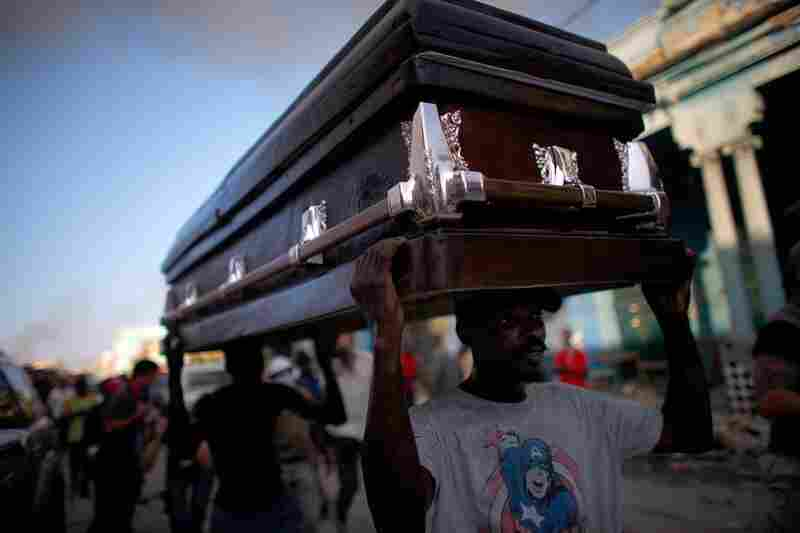 Haitian men carry a coffin on Monday in downtown Port-au-Prince.