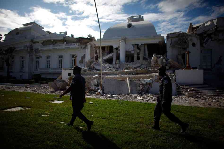 Security guards walk on the lawn in front of the destroyed National Palace Tue