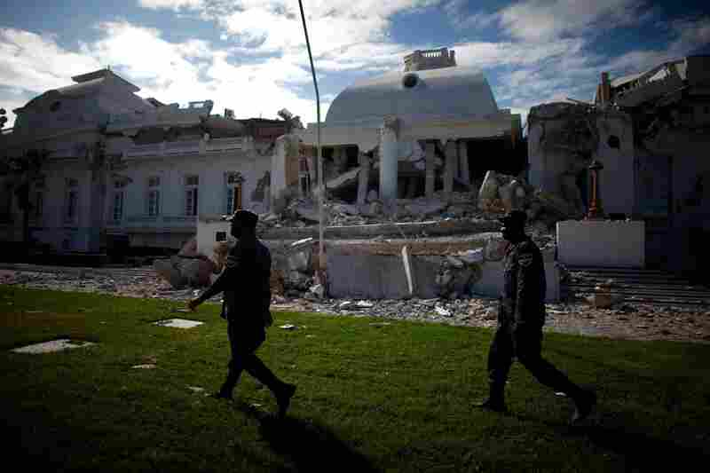 Security guards walk on the lawn in front of the destroyed National Palace Tuesday in Port-au-Prince.