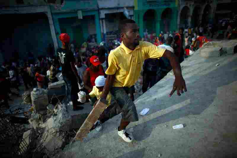 One Haitian man attacks another, in a dispute over goods from a collapsed supermarket in Port-au-Prince, on Wednesday.