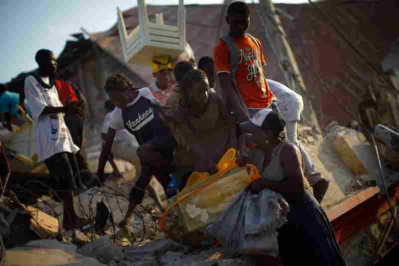 Haitians scramble off the roof of a collapsed supermarket, their arms full of items lifted from the store.