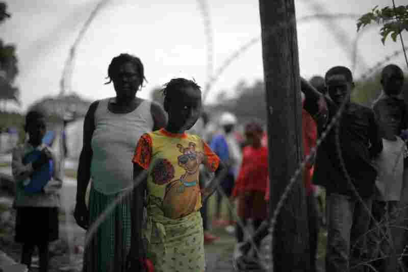 A girl peers though the wire separating the tent city from the field hospital.