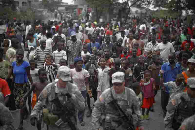 A growing group of Haitians follows the 82nd Airborne division convoy, in charge of protecting the field hospital, down the street.