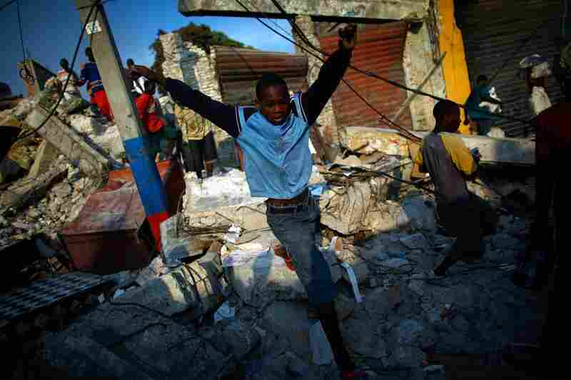 A boy jumps from a pile of rubble after police fired shots in the commercial district of downtown Port-au-Prince.