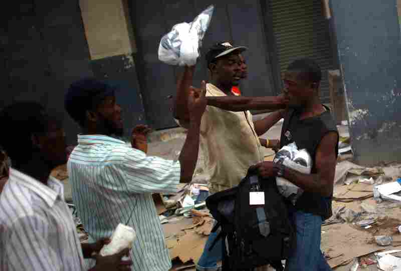 Men fight over shoes procured from the rubble of the market.