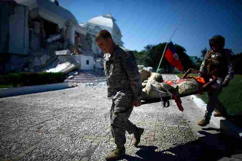 U.S. soldiers transfer patients to a staging area in front of the National Palace.