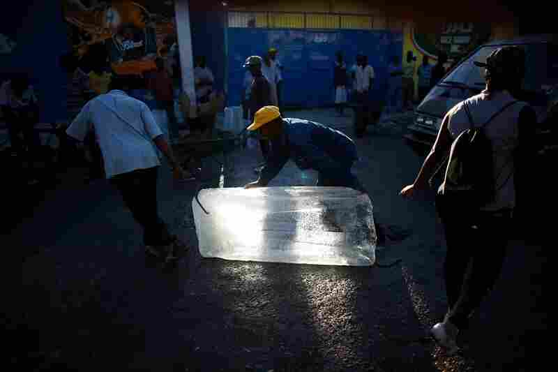Men move blocks of ice from the only functioning ice plant in the city. Without power, it's the only way to keep food cool.