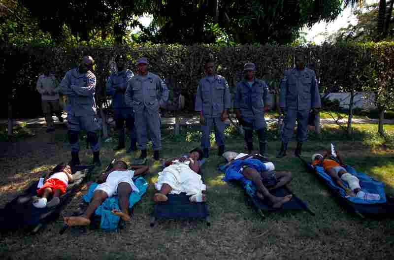 Haitian National Police stand over patients in front of the National Palace waiting to be evacuated Thursday.