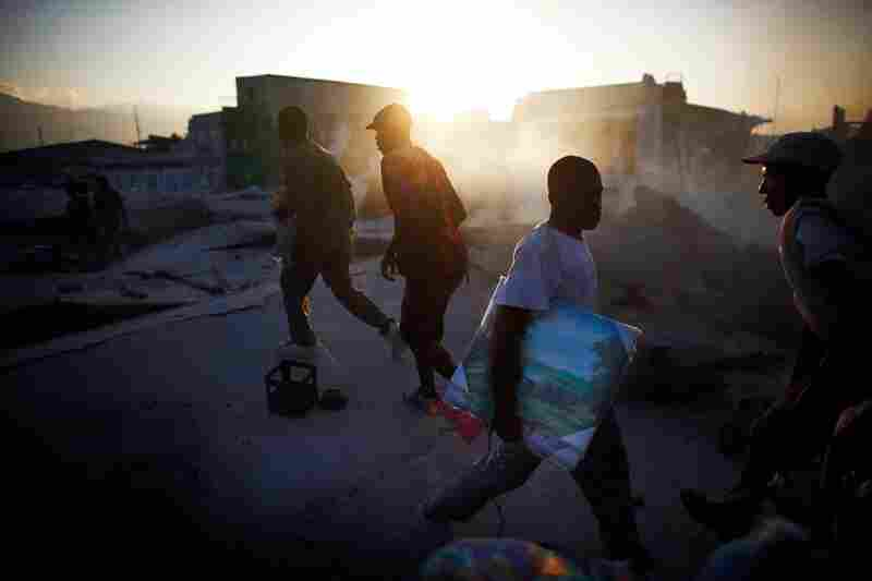Men walk across the roof of a collapsed supermarket in Port-au-Prince Wednesday.