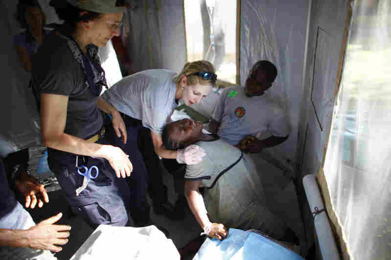 Expectant mother Veda Brazile writhes in pain from contractions in a medical tent at the HHS field hospital. Goodman (left) oversees her birthing process.