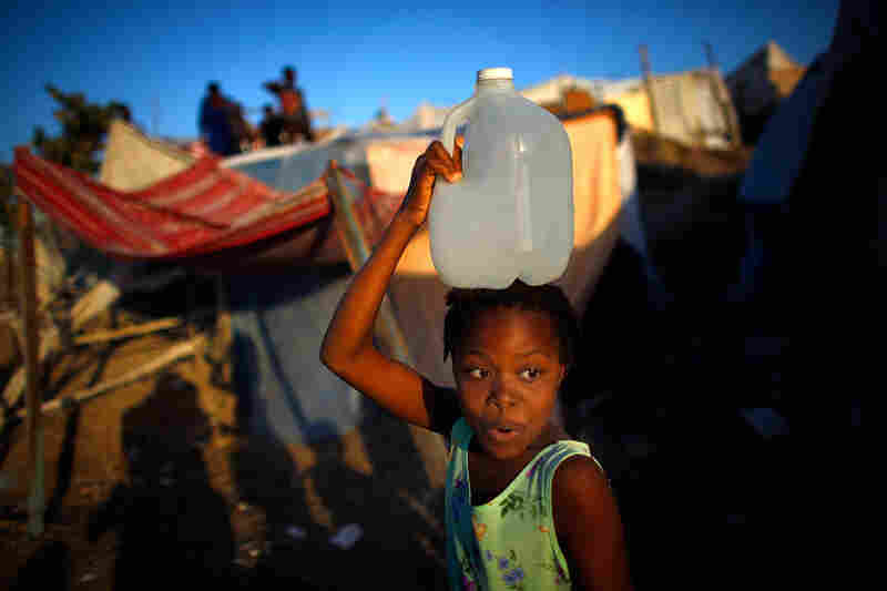 A Haitian girl carries a jug of clean water through a village of tents.