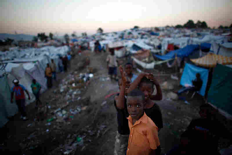 Haitian boys stand idly in a displacement camp. As many as 200,000 people have fled Port-au-Prince, USAID reports.