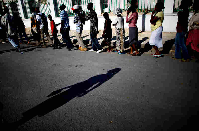 Haitians stand in line as peacekeepers from the United Nations World Food Program distribute water and humanitarian rations in front of the National Palace.
