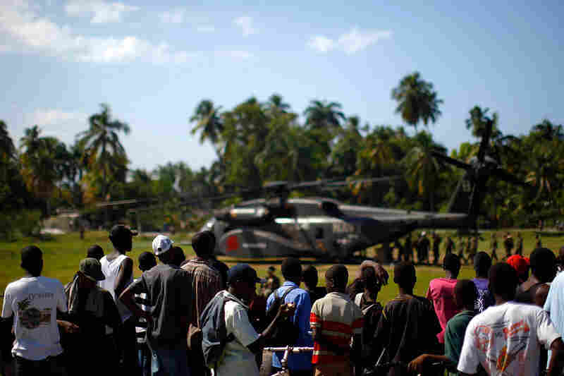 U.S. Marines unload a Navy Sea Stallion helicopter with relief supplies near the town of Leogane on Saturday. Aid is beginning to arrive with more frequency nearly two weeks after the 7.0-magnitude earthquake first struck.