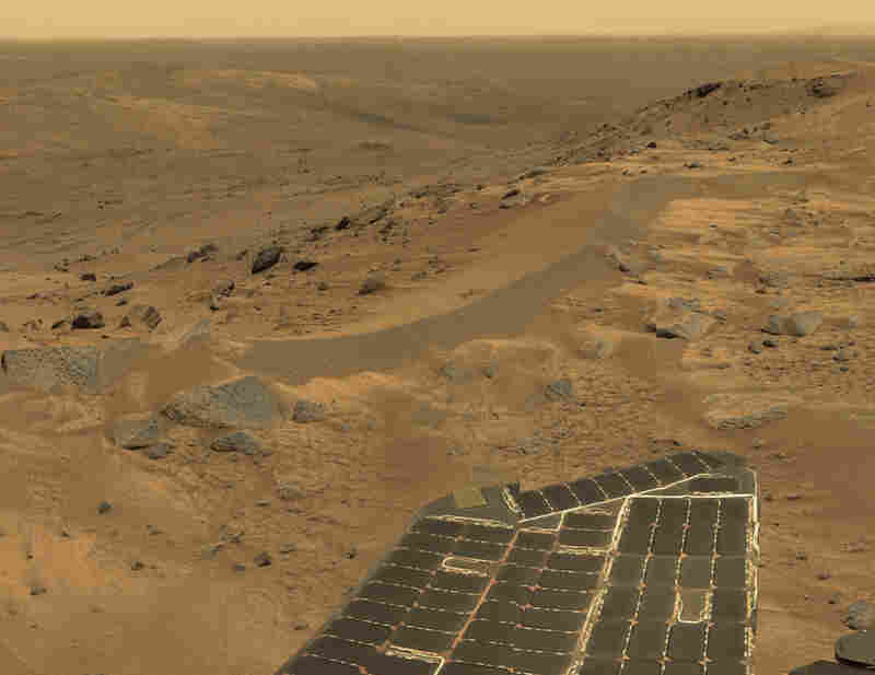 "A view from high in Mars' Columbia Hills, looking over Spirit's right solar panel ""wing"" and down into the Tennessee Valley. Just like on Earth, hills and ridges on Mars are windy places. The wind creates sand dunes and scours rocks, and it sometimes even cleans the dust off the rover's solar panels — increasing the electrical power and longevity of the mission."
