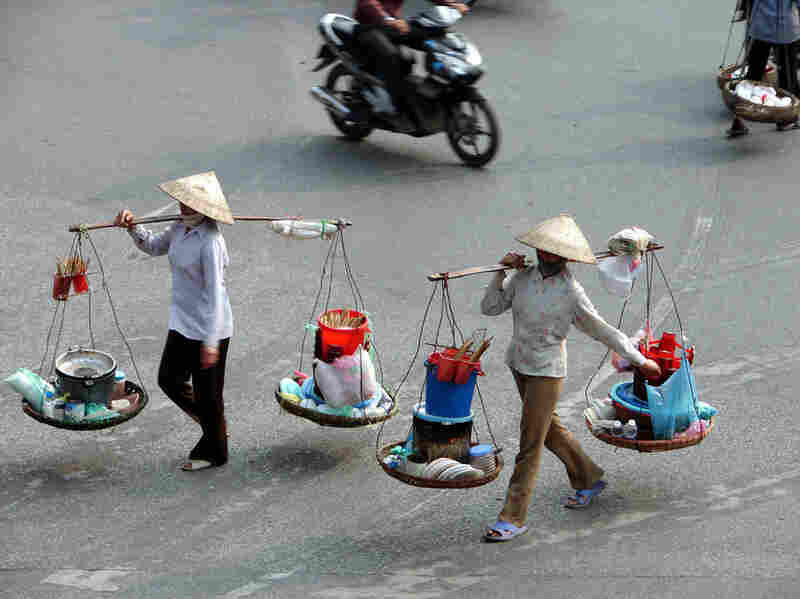 Vietnamese street vendors carry ingredients and cooking utensils to create banh khoai pancakes and other dishes.
