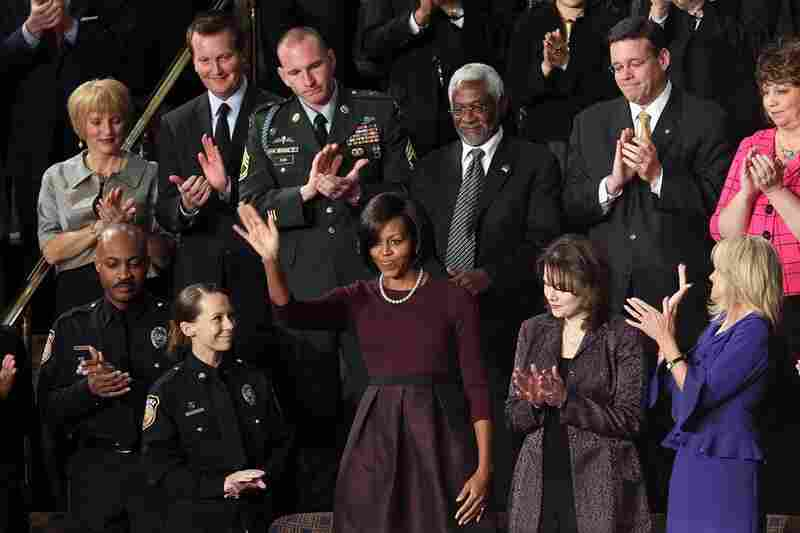 First lady Michelle Obama reacts to applause. At left: Officers Mark Todd and Kimberly Munley of Killeen, Texas. Directly above the first lady: Haitian Ambassador Raymond Joseph. At right: Rebecca Knerr and Jill Biden.