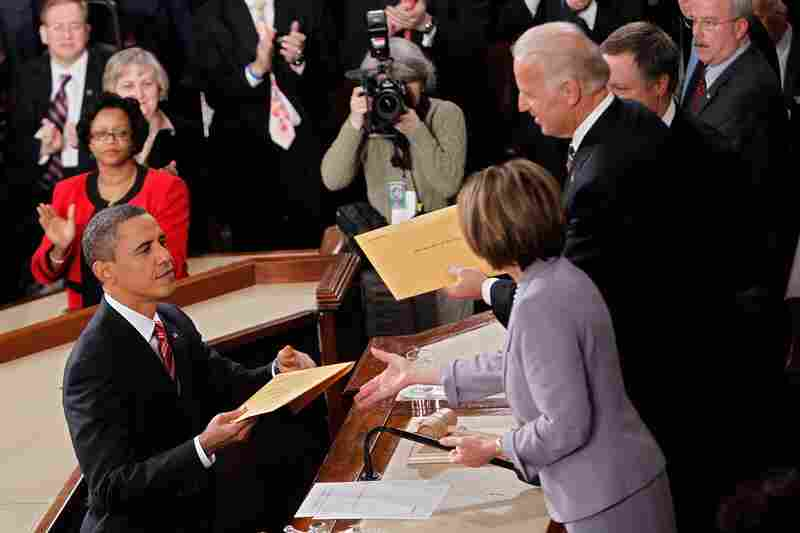 Obama hands copies of his speech to Biden and Speaker of the House Nancy Pelosi.