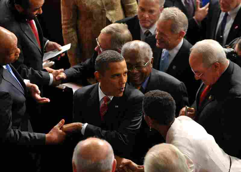 The president shakes hands on his way out of the chamber following his speech.