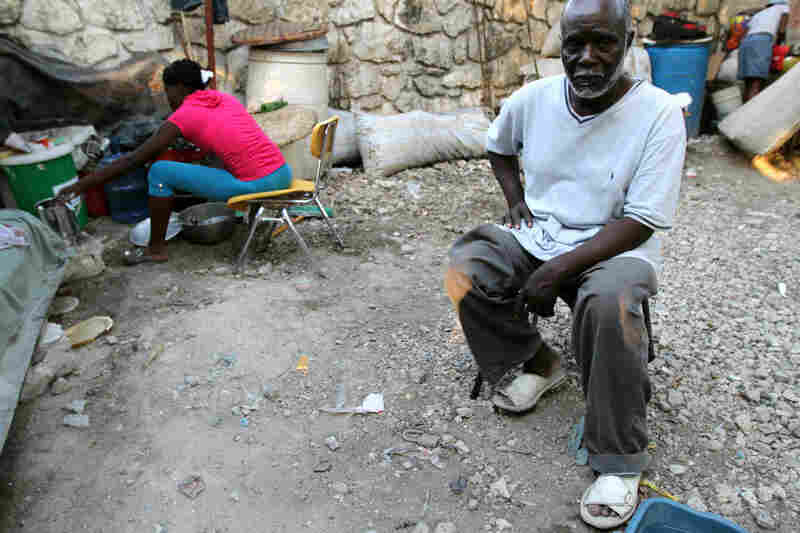 Max Paul sits in his makeshift camp. Paul, a pastor at the Church of God, lost his wife and six other people who lived in his house.
