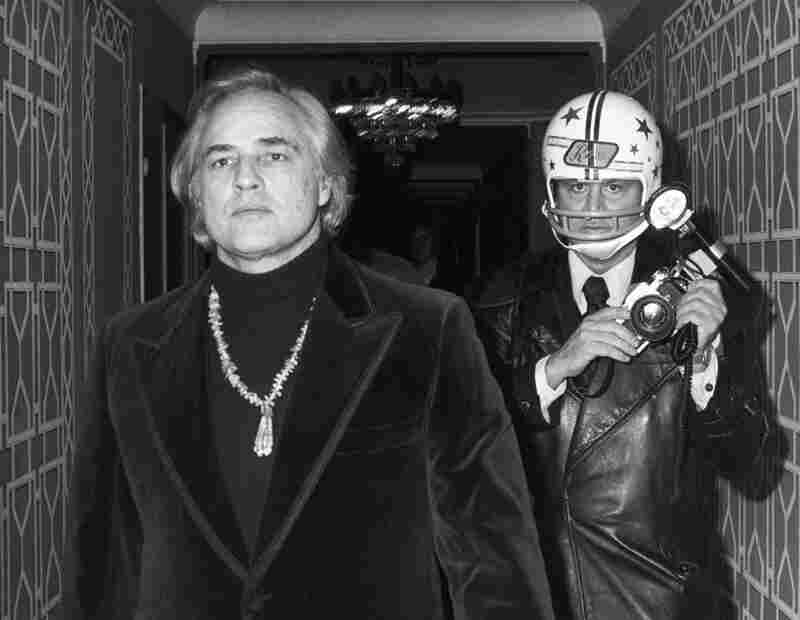 Galella, with Marlon Brando, wears a helmet to mock the fact that Brando had punched him the previous time he tried to photograph him.