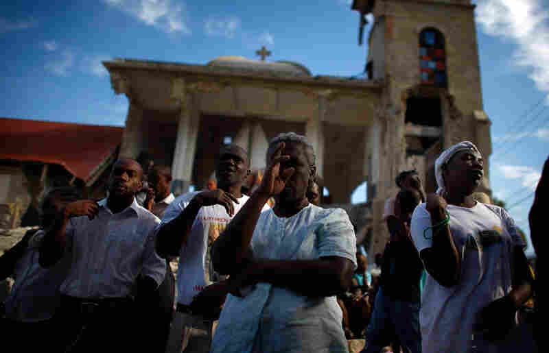 Haitians pray outside of the collapsed Sacre Coeur church in Port-au-Prince. The three-day mourning period included prayer, song and a moment of silence at the time of the quake.