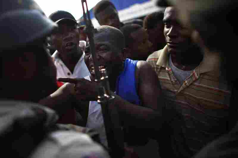 A man yells in the face of police officers as a group of men protest the living conditions of the refugee camps in Port-au-Prince.