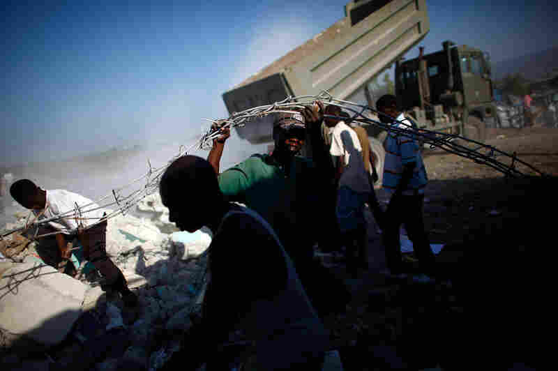 Scavengers scramble for scrap metal as a dump truck empties its load at Jeremy Wharf near Port-au-Prince. City authorities are still unsure about where they will put the waste, adding to the logistical problems overwhelming Haiti after the earthquake.