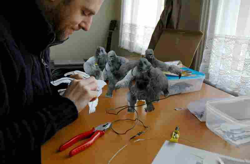 Hill attaches Blu-Tack and wire to images of Yetis.