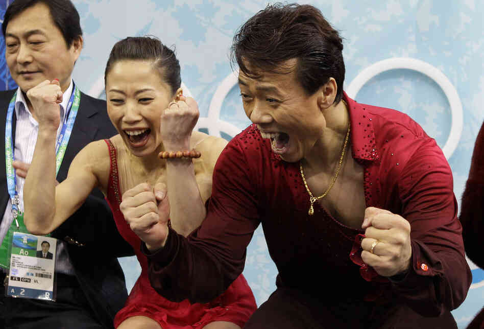 Figure skaters Shen Xue and Zhao Hongbo of China react to their winning score after performing their pairs free program. The husband-and-wife team took the gold in pairs figure skating.