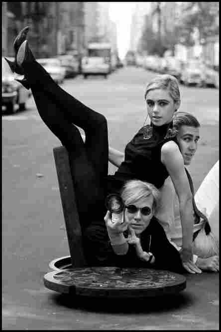 Artist Andy Warhol emerges from a city sewer and poses with Edie Sedgwick and Chuck Wein in New York City in 1965. Burt Glinn's photography included pop artists like Warhol, as well as political figures like Fidel Castro.