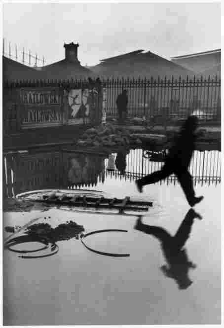 "This photograph, one of the most iconic from the past century, was taken by another Magnum founder, Henri Cartier-Bresson — often called the father of modern photojournalism. Captured at the ""decisive moment,"" a man leaps over a puddle in rainy Paris in 1932."