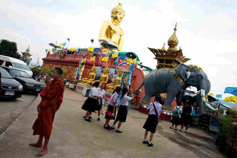 Schoolgirls take photographs of the elephant statue near the giant golden Buddha at Sop Ruak.