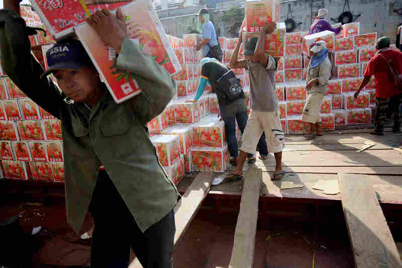 Dock workers unload fruit from a Chinese freighter at Chiang Saen's port on the Mekong River.