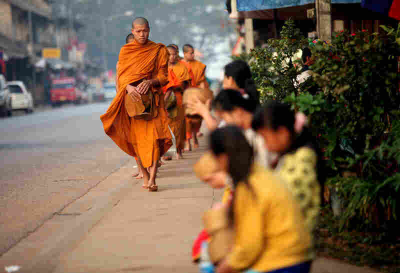 Buddhist monks receive alms at sunrise in Luang Prabang.
