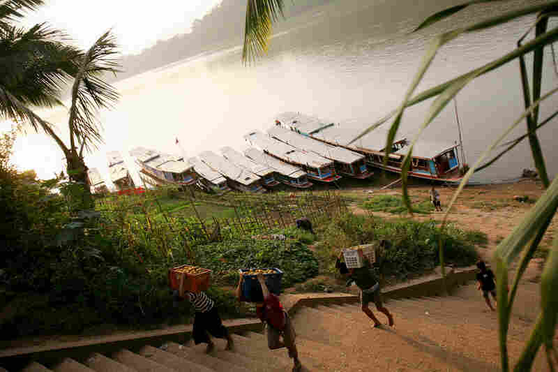 Workers unload produce from boats at a dock on the Mekong in Luang Prabang, Laos.