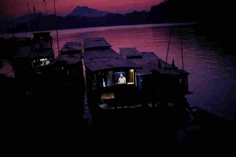 At sunset, a woman works on her boat on the Mekong in Luang Prabang.