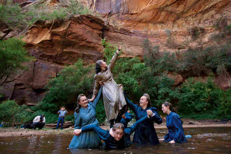 """Female FLDS members wear modest attire like ankle-length prairie dresses, even while swimming. """"It can get kind of cold,"""" says Verda Shapley, 19, reaching for a cable trolley with her sisters at a pond near Hildale. """"We do everything together,"""" says their father, William (at left). """"The foundation of this life is your belief in a life after this."""""""