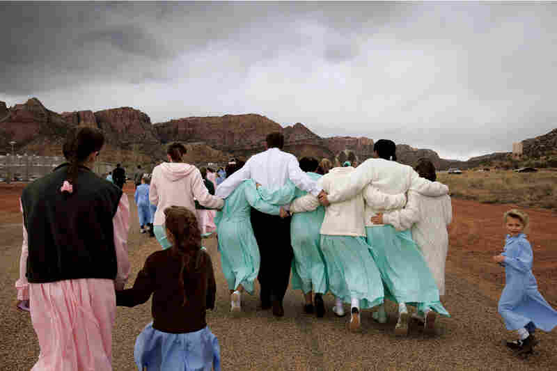 """An FLDS man leaves a funeral service, linking arms with six of his wives. Only men deemed """"godly"""" are permitted to enter into plural marriage by the church leader; those later judged unworthy can have their wives and children reassigned to other men."""
