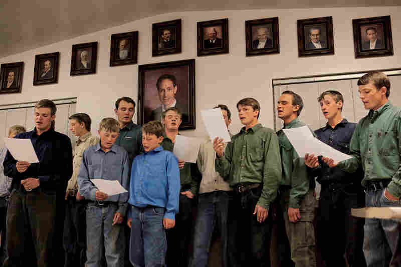 """""""Singing is a nice way to wind down the day, but it's hard to manage during harvest time,"""" says Aaron Jessop Jr. He stands beneath a large picture of Warren Jeffs, the former president of the FLDS, who is serving a prison sentence for arranging marriages with underage girls."""