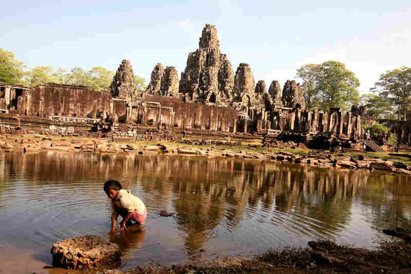 A girl looks for crayfish in a pond in front of Angkor's Bayon temple, near Siem Reap. The Bayon is a 12th century Buddhist temple that is said to represent the intersection of heaven and earth.