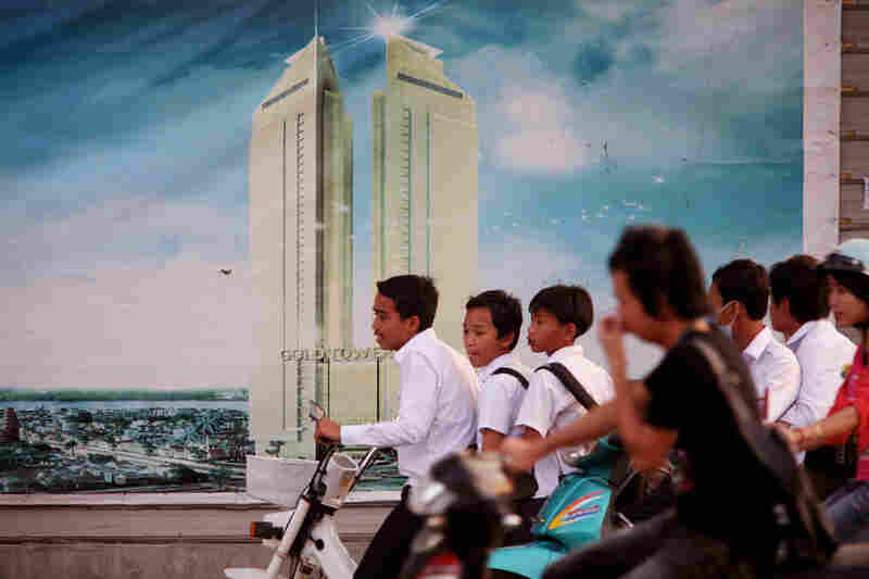 Cambodian teens on motorbikes drive past a billboard for the new Gold Tower 42, soon to be Phnom Penh's newest and tallest skyscraper.