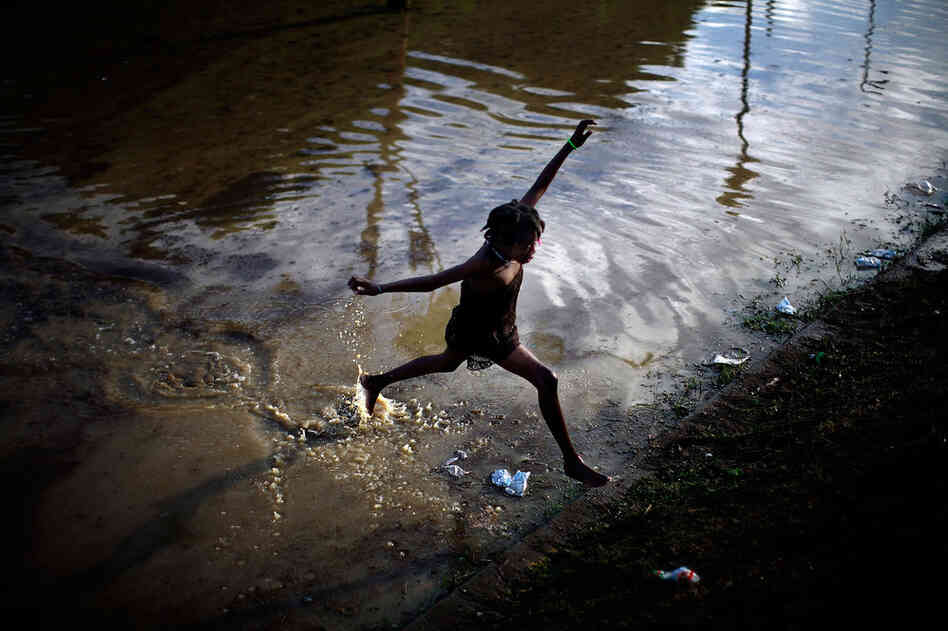 As if the Jan. 12 earthquake weren't devastating enough, Haiti now faces the rainy season, which usually begins in late spring. After heavy rains overnight Wednesday and Thursday, a girl jumps across a flooded field containing the sewage runoff from the Mais Gate tent city near the airport in Port-au-Prince.