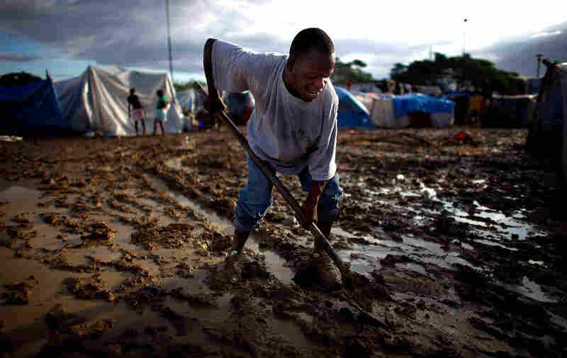 A Haitian man attempts to dig a trench in the mud to alleviate the flood damage. As the heavy rains begin, the question is no longer simply how to find housing for Haitians, but also how to keep them dry.