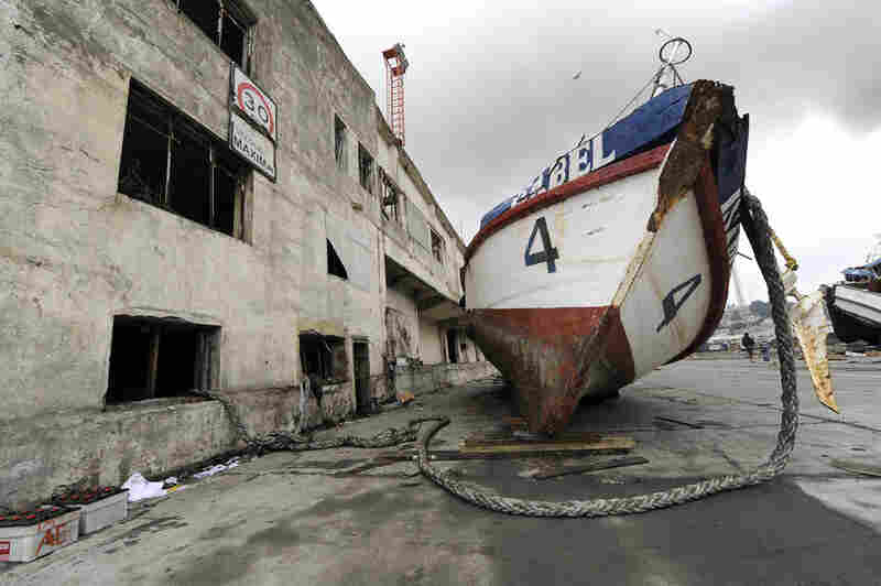 A boat rests next to a building Monday after it was washed ashore by the tsunami in Talcahuano.