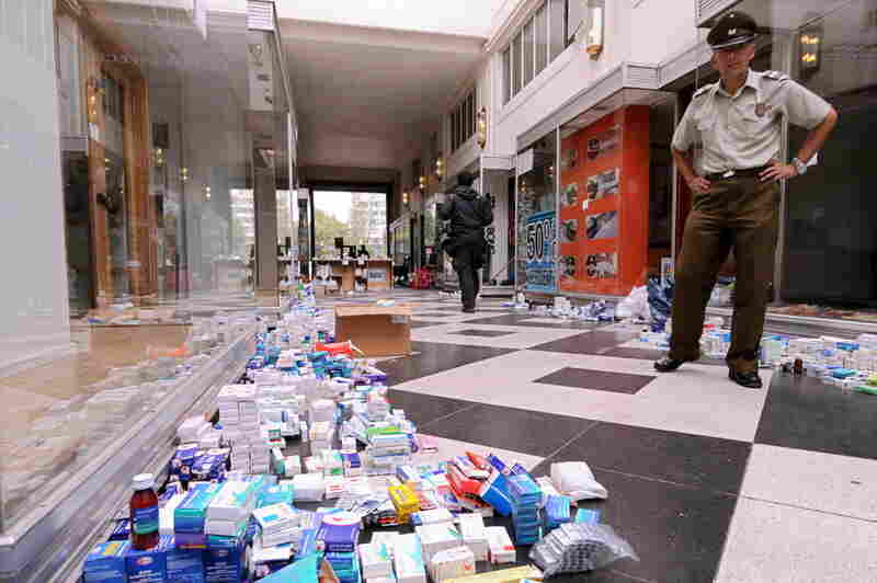 A policeman stands near medicine and other items donated Wednesday for earthquake victims.
