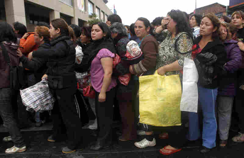 People wait for supplies in front of a supermarket in Concepcion.