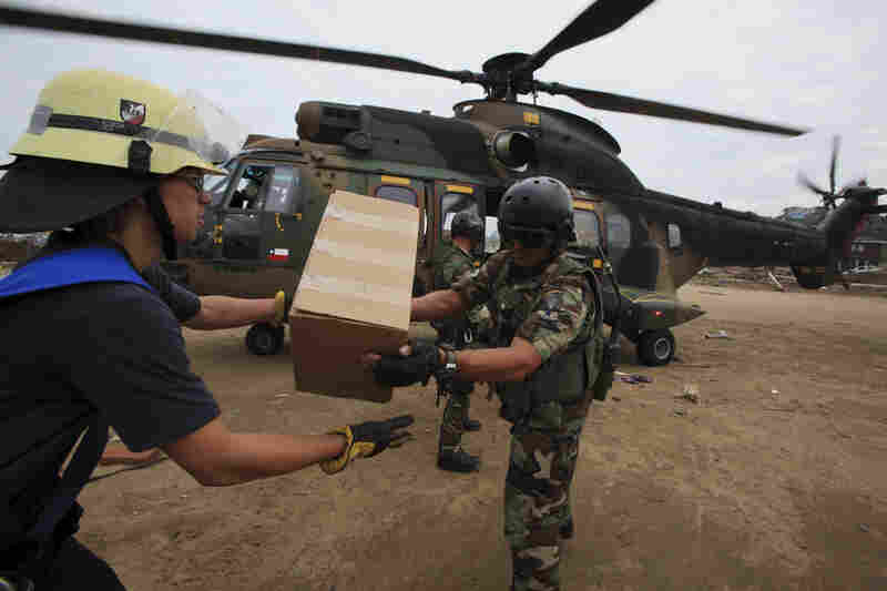 Chilean troops and firefighters unload relief supplies Wednesday from a military helicopter in the coastal town of Dichato, which was heavily damaged by tsunami waves produced by Saturday's 8.8-magnitude earthquake.