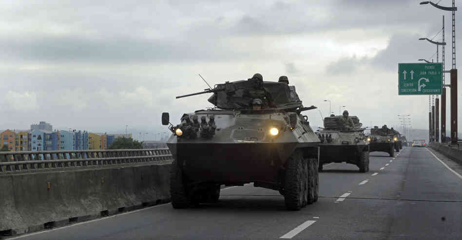 Chilean army armored personnel carriers drive along a bridge Tuesday in Concepcion, the country's second-largest city. Bachelet said Chile has dispatched 14,000 to devestated areas.