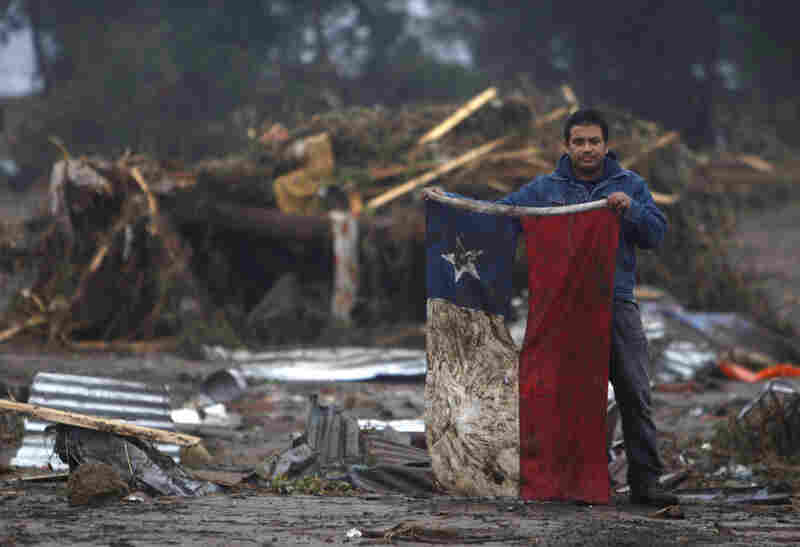A man holds a torn and soiled Chilean flag on Sunday in a flooded area of Pelluhue, about 200 miles southwest of Santiago.